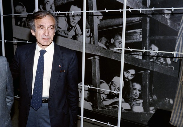 """1986 Nobel Peace prize winner and writer Elie Wiesel (L) stands in front of a photo of himself (bottom right hand corner) and other inmates, taken at the Buchenwald concentration camp in 1945, during his visit on December 18, 1986 to the Holocaust Memorial Center """"Yad Vashem"""" in Jerusalem. Wiesel, a naturalized American citizen, was born 30 September 1928 in Sighet (Romania). A survivor of the Nazi concentrations camp, he has spent his adult life fighting for the rights of Holocaust victims. SVEN NACKSTRAND/AFP/Getty Images)"""