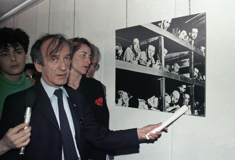 Elie Wiesel, winner of the 1986 Nobel Peace prize, views the Holocaust Memorial in Lyon, France, June 2, 1987. The photo on the wall shows prisoners of the German Buchenwald concentration camp inside their barracks, a few days after U.S troops liberated the camp near Weimar, Germany. Wiesel points to the picture of himself in the camp. (AP Photo/Laurent Rebours)